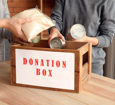 Volunteers putting donation food into box at table